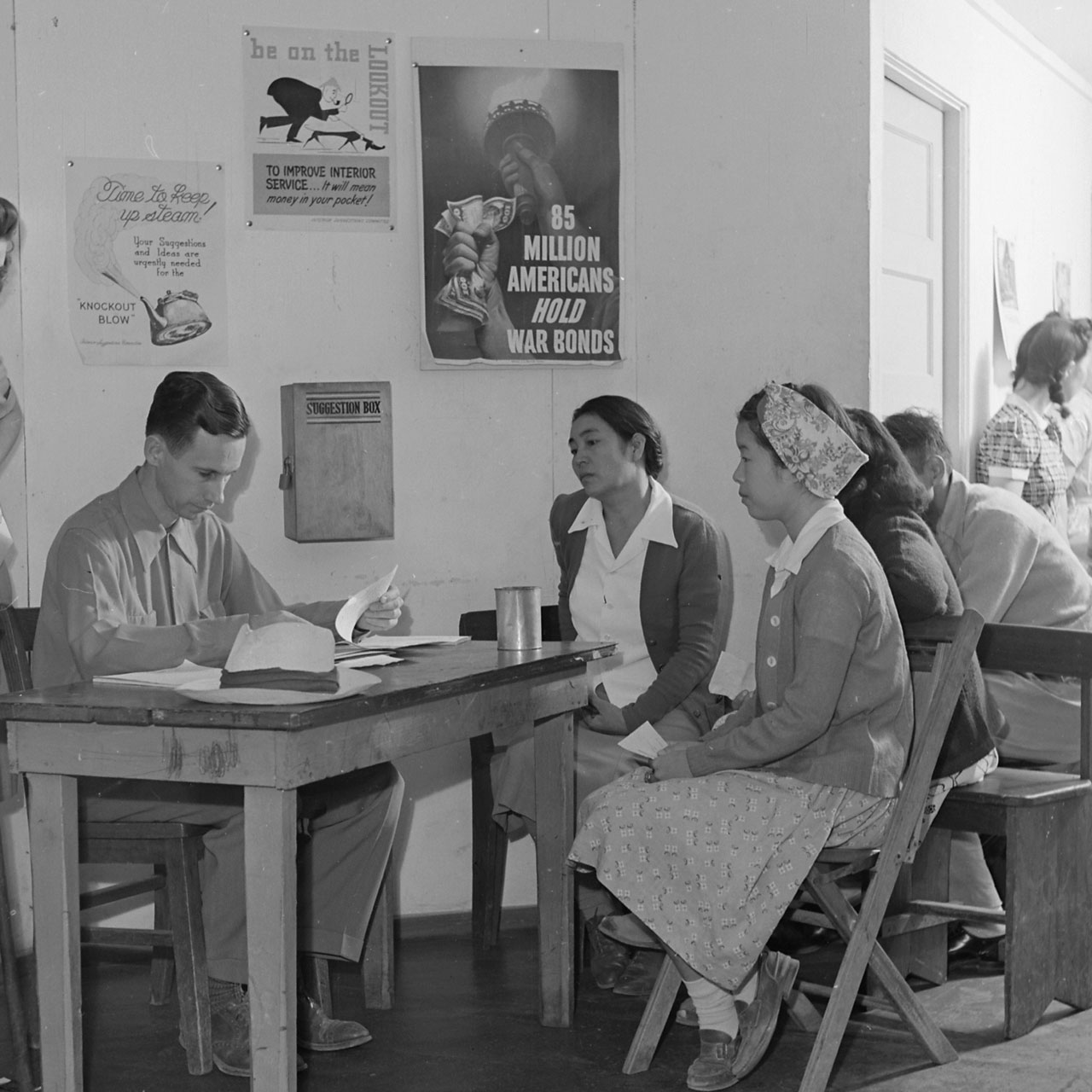 Poston,_Arizona._Evacuees_waiting_in_line_inside_the_administration_building._These_lines_for_eve_._._._-_NARA_-_539876