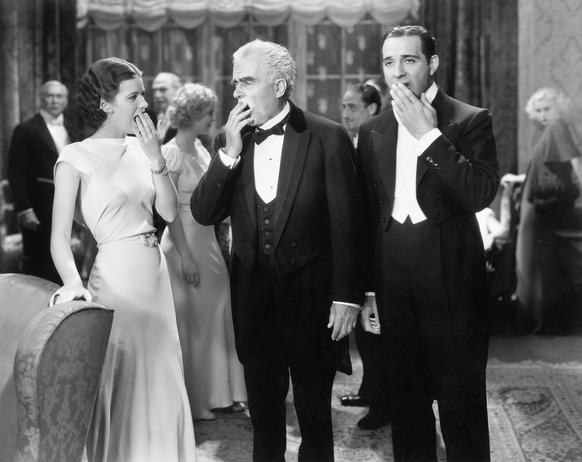 Three people standing together at a formal party yawning and being bored